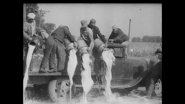 / women protesting the lack of money food or bread for their families / farmhands on the back of a truck pouring cans of milk onto the road / man... - 1935 stock videos & royalty-free footage