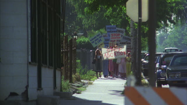 MS TS Women  protestors marching to portest against abortion carry signs board and yelling