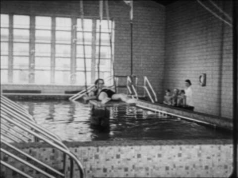 stockvideo's en b-roll-footage met women pulling child with polio on platform into pool for water therapy / indiana / newsreel - polio
