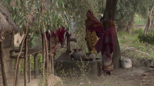 WS Women pumping  water from village well into clay water pots / India
