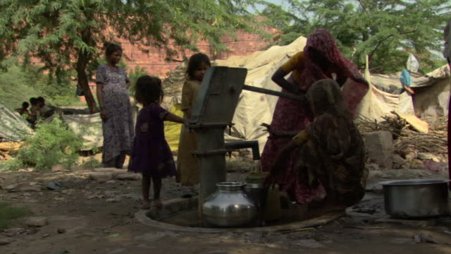 ws women pumping water from village well with two girls looking on, agra, uttar pradesh, india - jug stock videos & royalty-free footage