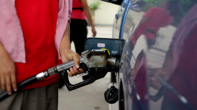Women pumps fuel at a gas station