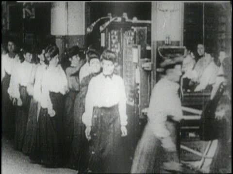 women punch time clocks in a factory - 1900~1909年点の映像素材/bロール