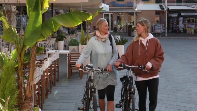 women push bikes through village piazza - 20 24 years stock videos & royalty-free footage