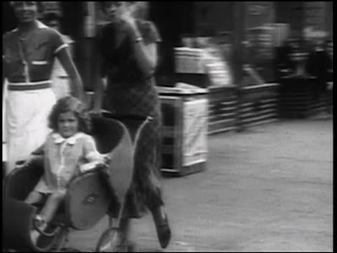 B/W 1938 PAN women pushing baby carriage on sidewalk / one woman smoking pipe / newsreel