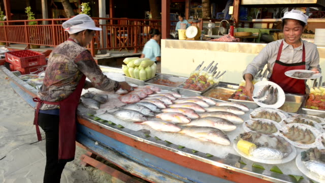Women put fresh fish and seafood on ice for barbecue
