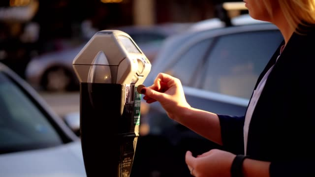 women putting coins into parking meter. - parking stock videos & royalty-free footage