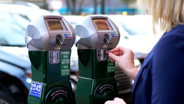 Women putting coins into parking meter.