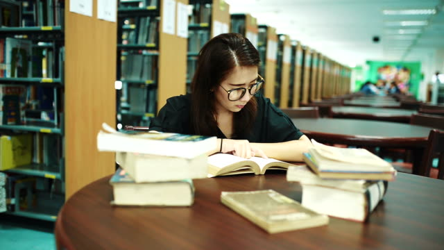 女性が図書館で本を読んで - 図書館点の映像素材/bロール