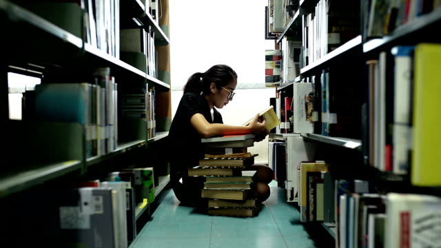 women reading a book at the library - picking stock videos & royalty-free footage