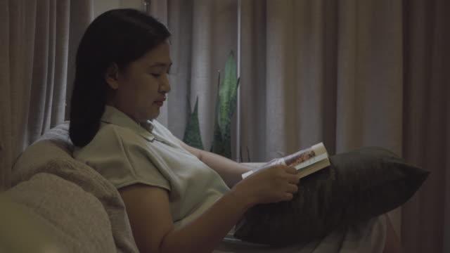 vídeos de stock e filmes b-roll de women reading a book on sofa - só mulheres jovens