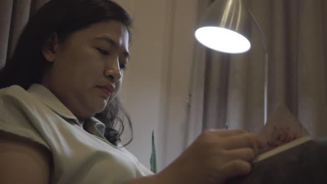 vídeos y material grabado en eventos de stock de mujeres leyendo un libro en sofa - sólo mujeres jóvenes