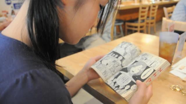 cu women reading comic book / los angeles, california, usa - 漫画点の映像素材/bロール