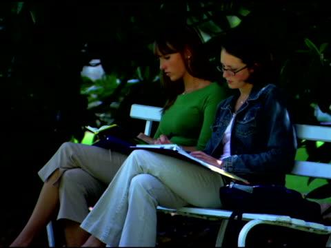 women reading on bench - three quarter length stock videos & royalty-free footage