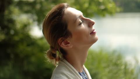 vídeos y material grabado en eventos de stock de las mujeres relajación en el lago - ojos cerrados