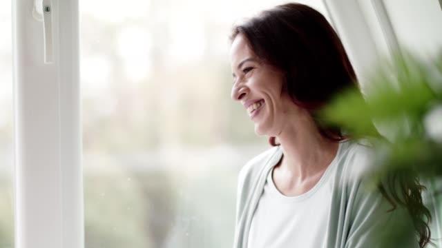 vídeos y material grabado en eventos de stock de mujeres relajantes por la ventana - 50 54 años