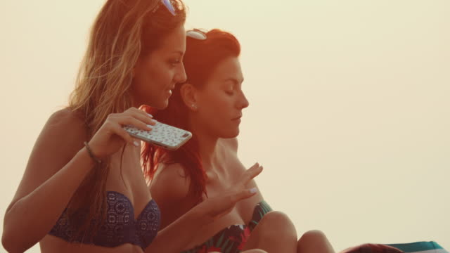 Women relaxing together on the beach at sunset