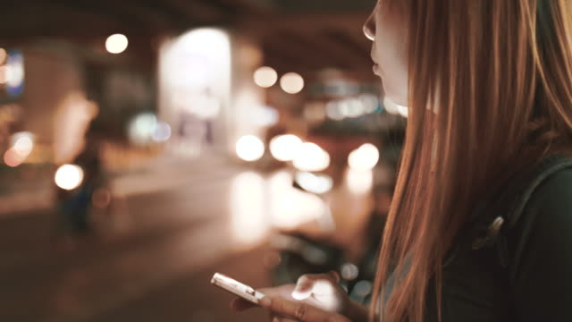 women requesting and waiting uber from a smart phone at night - crowdsourced taxi stock videos and b-roll footage