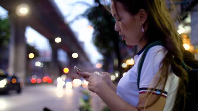 Frauen anfordern und warten Uber über ein Smartphone in der Dämmerung