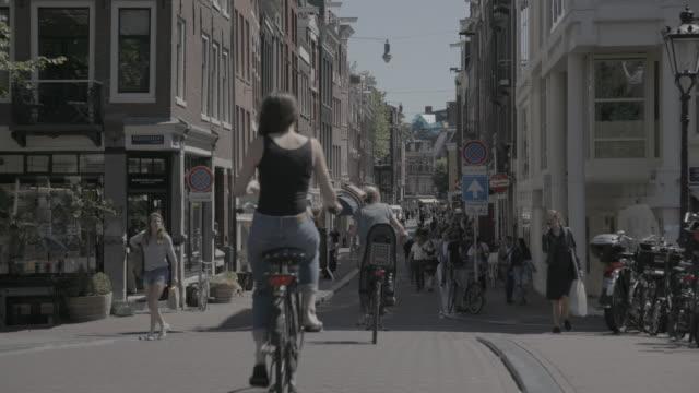 Women ride bikes down crowded street full of pedestrians in Amsterdam, wide shot
