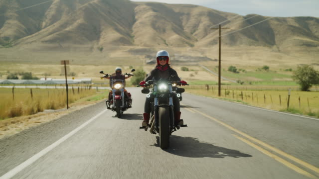 vidéos et rushes de women riding motorcycles on remote road with arms raised / payson, utah, united states - payson