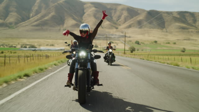 women riding motorcycles on remote road with arms raised / payson, utah, united states - 腕を上げる点の映像素材/bロール