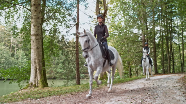 DS Women riding on trotting white horses by a lake