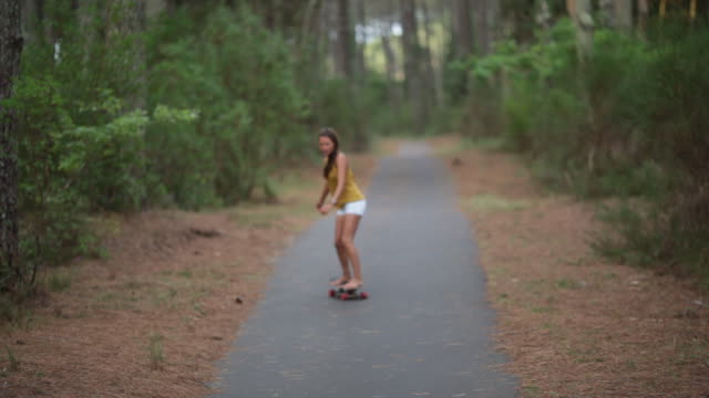 Women riding skateboard in the summer in the forest in the south of France.