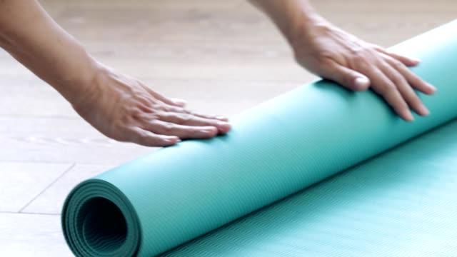 women rolls her yoga exercise mat, getting prepared for practice - recreational pursuit stock videos & royalty-free footage