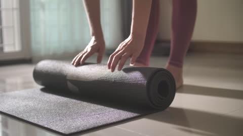 vídeos y material grabado en eventos de stock de las mujeres enrollan su estera de ejercicio de yoga, preparándose para la práctica - yoga