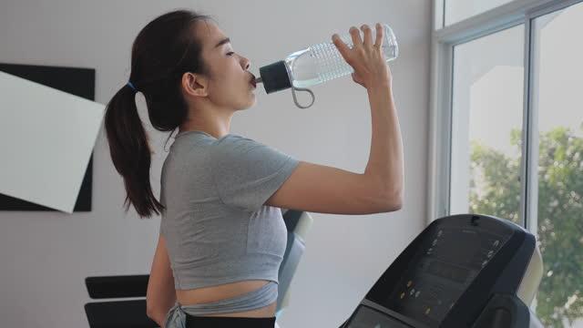 stockvideo's en b-roll-footage met vrouwen die lopen en een onderbreking om water te drinken - jogster