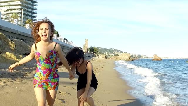 vidéos et rushes de femme jogging sur la plage. ralenti - trébucher
