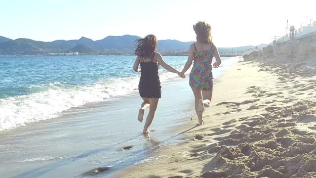 Women running on the beach. Slow motion