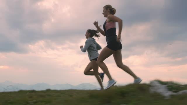SLO MO Women running on the top of a mountain ridge