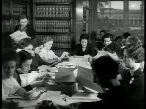 Women seated at large oval table covered w/ papers briefs books on shelves BG suggest Law Library Woman sorting papers into boxes Women seated at...