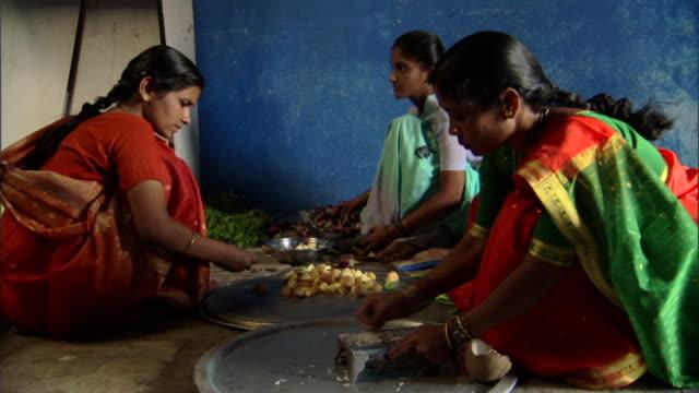 MS Women seated on ground preparing food for celebration, Pune, Maharashtra, India