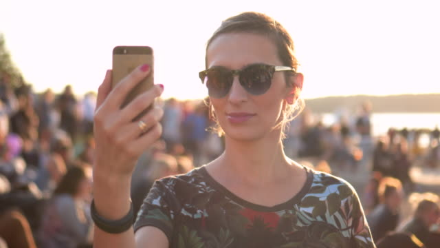 Women Selfie with sunset and crowd