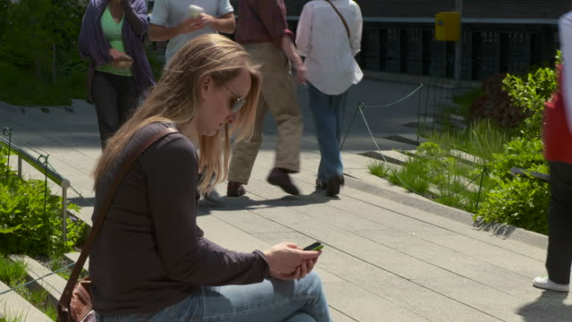 women sending a text on her phone while sitting on a park bench on the highline park in new york. - three wheeled pushchair stock videos & royalty-free footage