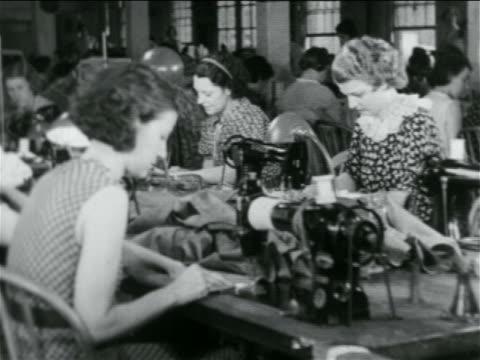 b/w 1934 women sewing at machines in wpa garment factory / documentary - 雇用促進局点の映像素材/bロール