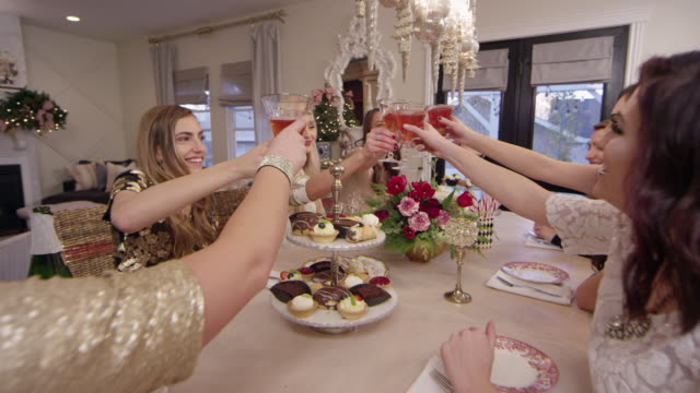 women share a toast at a holiday christmas party - utensil stock videos & royalty-free footage