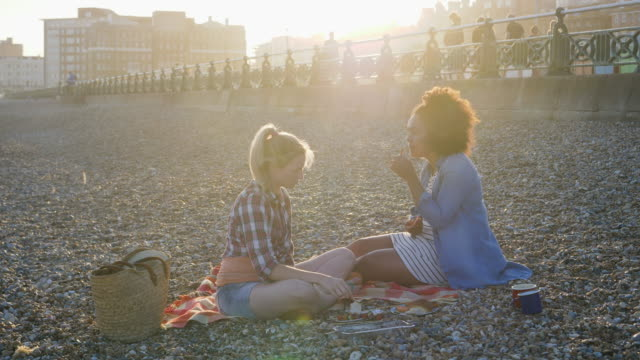 Women sharing barbecue food , sitting on beach in sunset.