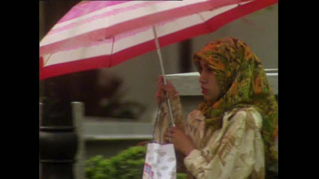 women shield from rain in kuala lumpur, malaysia; 1996 - 1996 stock videos & royalty-free footage