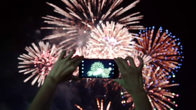 Women shooting fireworks with smartphone