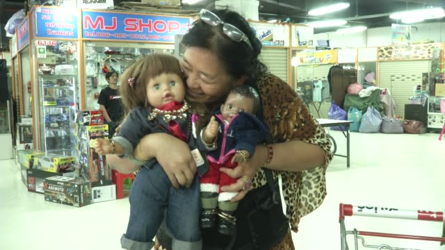 women shop and care for luk thep dolls literally translates as child angels and people believe they bring good fortune and they are pampered by their... - skämma bort sig bildbanksvideor och videomaterial från bakom kulisserna