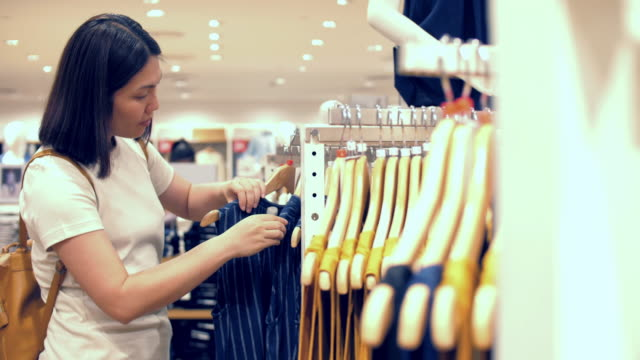 women shopping and choosing a shirt in shop store - clothes shop stock videos & royalty-free footage