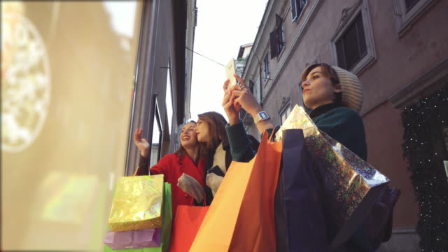women shopping during winter sales in rome, italy - comprare video stock e b–roll