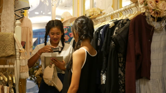 women shopping in boutique and use Credit card reader