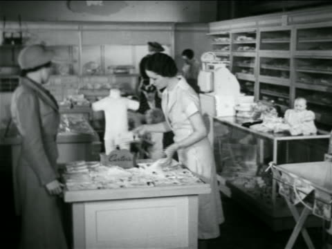 b/w 1938 women shopping in infant clothing department of department store / industrial - department store stock videos & royalty-free footage