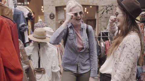 women shopping in vintage shop, trying on sunglasses and hat. - shop stock videos & royalty-free footage