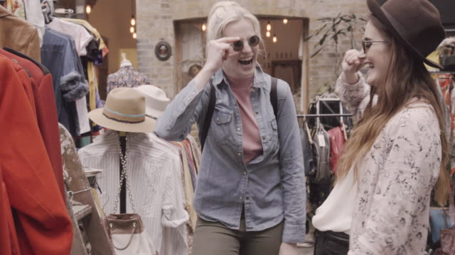 vídeos de stock, filmes e b-roll de women shopping in vintage shop, trying on sunglasses and hat. - fora de moda estilo